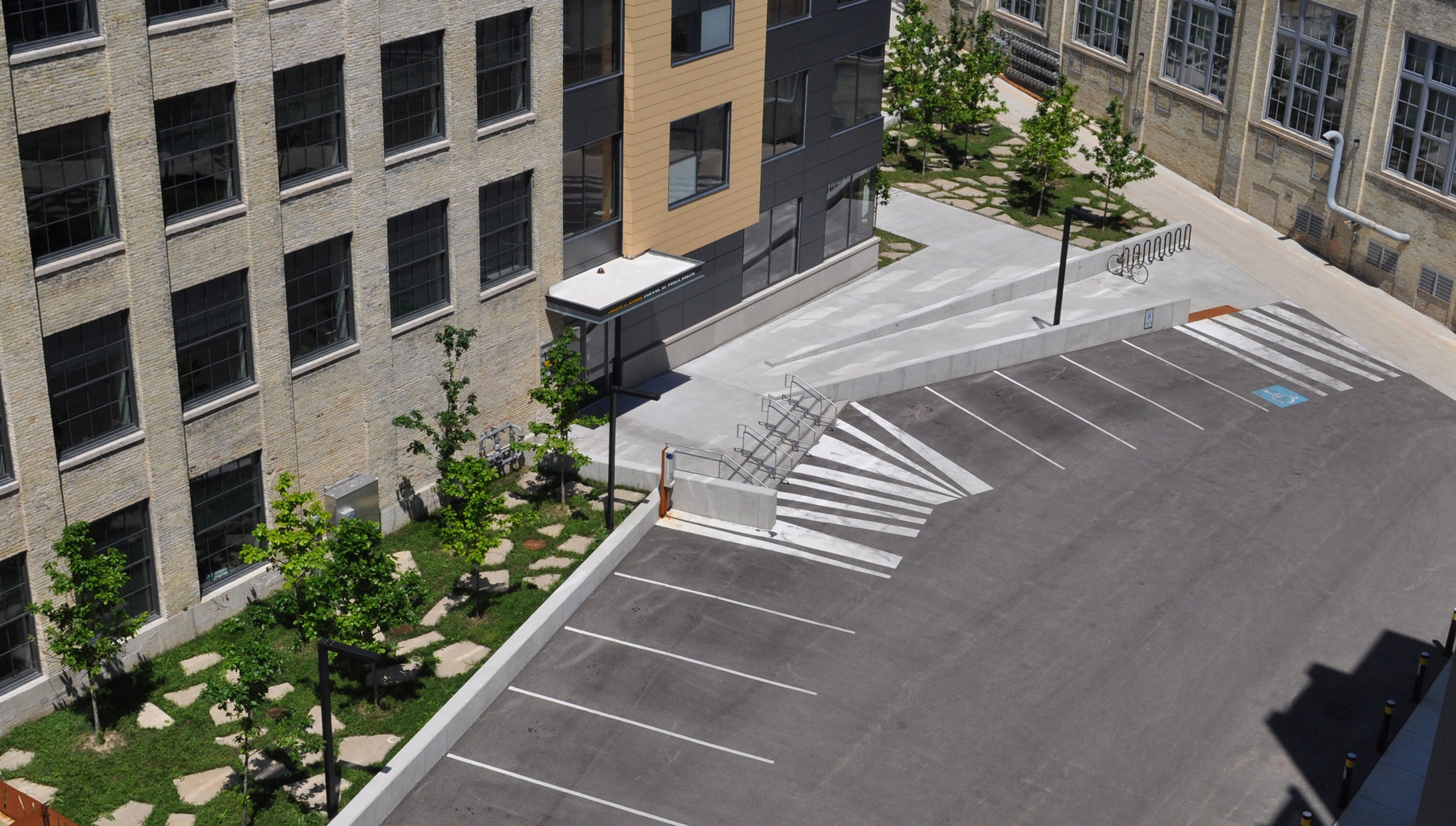 LEVERAGING THE MUNDANE: Required accessible ramps, parking spaces and stripes are reimagined to create a dynamic landscape forecourt and series of occupiable sloping terraces.